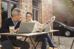 Happy mature couple reading newspaper with laptop in back yard Stock Photos