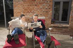 Mature couple reading newspaper while sitting in back yard Stock Photos