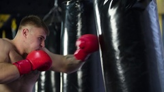 Boxer training punching bag HD slow motion close-up video. Fighter blows punch Stock Footage