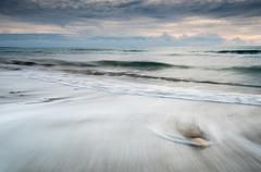 Pebbles in the beach and flowing sea water Stock Photos