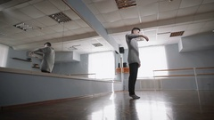 The professional dancer rehearses at a mirror. He does the smooth and exact Stock Footage
