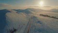 Several cars driving on icy road at the dusk near the mountains. Stock Footage