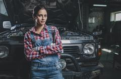Portrait of confident female mechanic with arms crossed leaning on car at Stock Photos