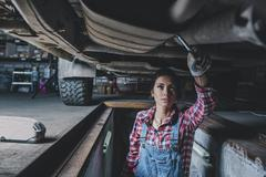 Female mechanic working underneath car at garage Stock Photos