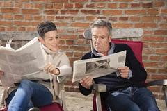 Man showing newspaper to woman while sitting in back yard Stock Photos