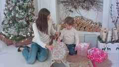 Cute little boy helping his mother to cut paper for wrapping up Christmas Stock Footage