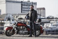 Full length portrait of biker holding helmet while standing by motorcycle Stock Photos
