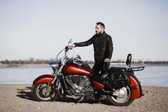 Full length portrait of biker standing by motorcycle and looking away at Stock Photos