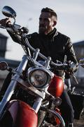 Portrait of biker sitting on motorcycle and looking away Stock Photos