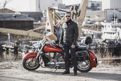 Full length portrait of biker standing by motorcycle against industrial setting Stock Photos