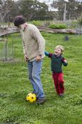 Full length of grandfather and grandson playing soccer on grassy field Stock Photos