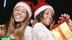 Happy Twin Sisters Holding Christmas Gifts Smiling In Slow Motion Stock Footage