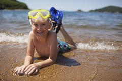 Portrait of boy with snorkel and swimming goggles lying on shore at beach Stock Photos