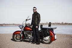 Full length portrait of biker standing by motorcycle at lakeshore Stock Photos
