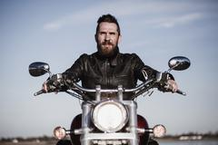 Portrait of confident biker sitting on motorcycle against sky Stock Photos