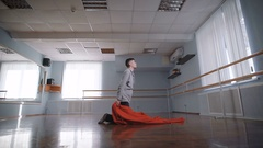 Dance with a big red cloth. The man falls on a red cloth. Beautiful movement Stock Footage