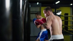Boxer training punching bag HD slow motion video. Fighter blows hook jab punch Stock Footage