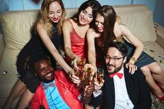 Cheerful young people enjoying party or booze Stock Photos