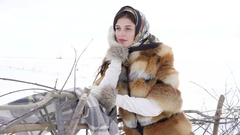 Young girl in winter clothes waiting near fence and looking aside 4K Stock Footage