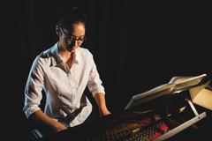 Woman playing a piano in music studio Kuvituskuvat