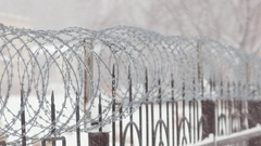 Barbed wire on metal fence with pointed rods. Snowing. Close. Stock Footage