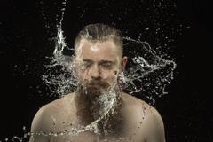 Water splashing on shirtless man's face against black background Stock Photos