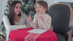 Young mother helping her struggling son to write a letter to Santa Claus Stock Footage