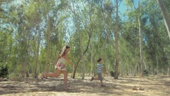 Children play catch-up in a sunny forest among the trees Stock Footage