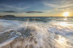 Waves crashing on the sandy beach framed by sunrise Stock Photos