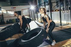 Determined male and female athletes flipping tire at health club Stock Photos