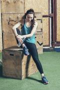 Full length of female athlete holding water bottle while sitting on wooden box Stock Photos
