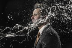 Water splashing on businessman against black background Stock Photos