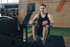 Determined man exercising on rowing machines at gym Stock Photos