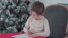 Concentrated little boy writing letter to Santa Claus at table Stock Footage