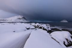 Storm clouds on the snowy peaks reflected in the cold sea at night Stock Photos