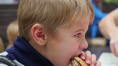The child eats a scone with chicken in the fast food restaurant Stock Footage