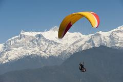 A tandem paraglider flys above Pokhara with views of the Annapurnas Stock Photos