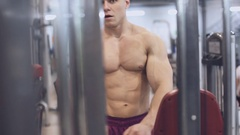 Muscular man doing exercise on triceps in the gym Stock Footage