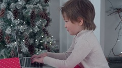 Smiling little boy typing letter to Santa Claus on a laptop near the Christmas Stock Footage