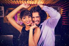 Composite image of cute couple dancing together on dance floor Stock Photos