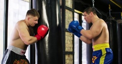 Two boxers training punching bag 4k video fight club. Trainer holds boxing bag Stock Footage