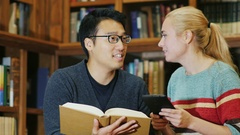 Smiling Korean man talking to a woman in the library. enjoy tablet Stock Footage