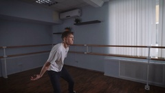 A young man performs the dance hip hop in the great hall. Dance movements with Stock Footage