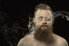 Water splashing on man's face against black background Stock Photos