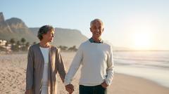 Senior couple enjoying a stroll on the beach Stock Photos