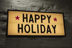 Close-up of Happy Holiday signboard against gray wall Stock Photos