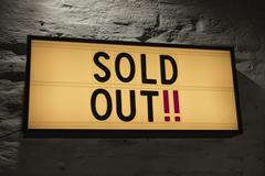 Close-up of Sold Out signboard against gray wall Stock Photos