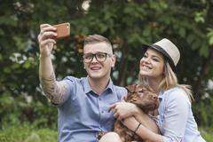 A couple with their Shar-pei/Staffordshire Terrier dog at the park taking a Stock Photos