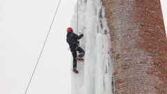 Ice climbing the icicle on the water tower. Tilting down. Stock Footage