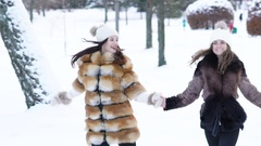 Two pretty girls running through the snow in park. Slowly Stock Footage